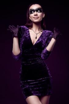 Elegante brünette frau im schönen kleid, paillettenmaske und handschuhe ergibt sich