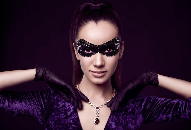 Elegante brünette frau im schönen lila kleid, paillettenmaske und schwarzen handschuhen