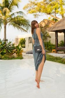 Elegante brünette frau im sexy kleid, das im stilvollen strandrestaurant im asiatischen stil aufwirft. volle länge.