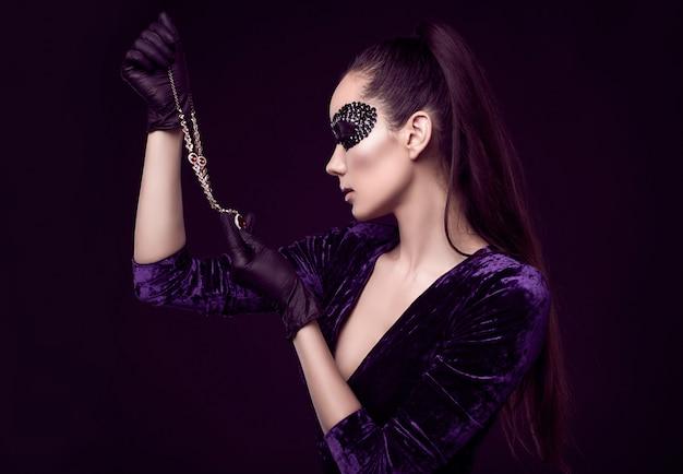 Elegante brünette frau in paillettenmaske mit schwarzen handschuhen schaut auf diamantkette