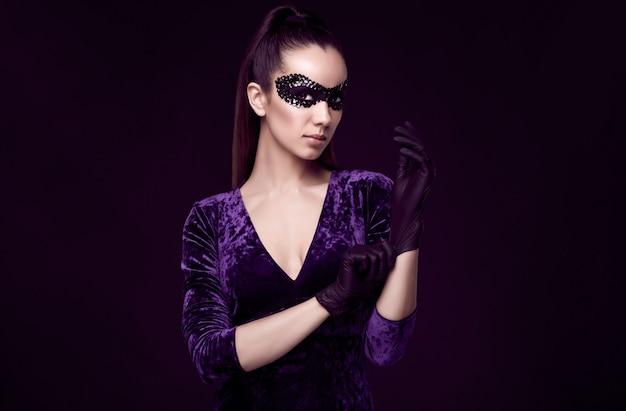 Elegante brünette frau in schönen lila kleid und pailletten maske handschuh nach oben