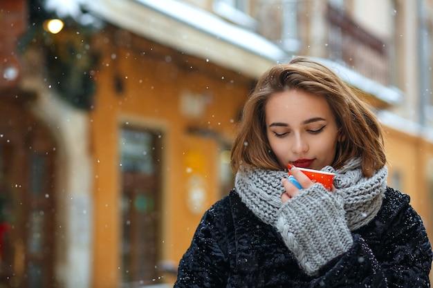 Elegante brünette frau trägt grauen schal und warmen mantel trinkt kaffee während des stadtspaziergangs. freiraum