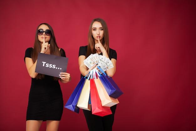 Elegante brünette frauen tragen schwarzes kleid, das einkaufstaschen hält, schwarzes freitag-konzept.