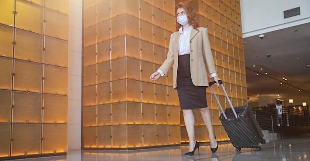 Elegante dame, die den sanitären vorsichtsmaßnahmen der pandemie folgt, indem sie eine medizinische maske in einer hotelhalle trägt