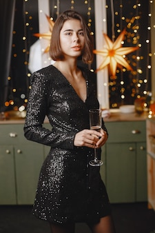 Elegante dame in der nähe von christmass tree. frau zu hause mit champagner.