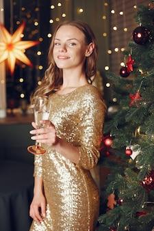 Elegante dame in der nähe von weihnachtsbaum. frau zu hause mit champagner.