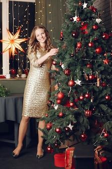 Elegante dame in der nähe von weihnachtsbaum. frau zu hause