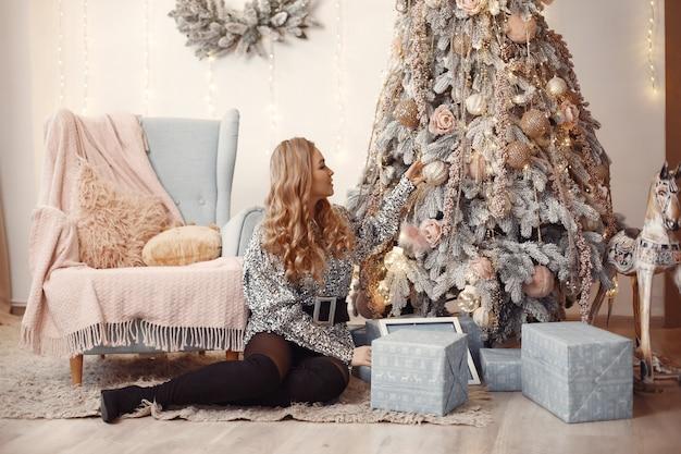 Elegante dame in der nähe von weihnachtsbaum