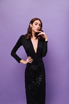 Elegante dame in glänzendem rock und schwarzer bluse sieht vorne aus
