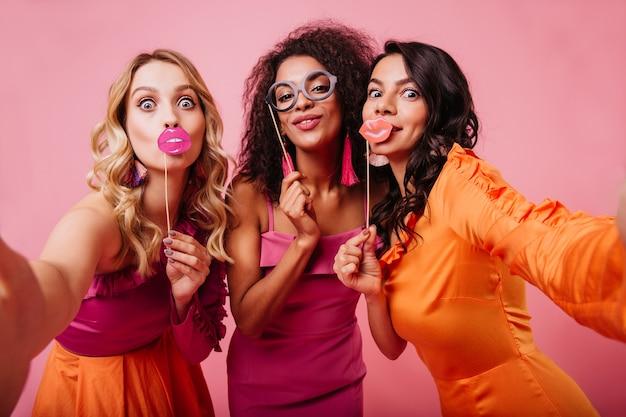 Elegante damen, die gesichter auf rosa wand machen