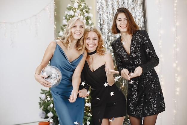 Elegante damen in der nähe von weihnachtsbaum. frauen in eleganter kleidung.