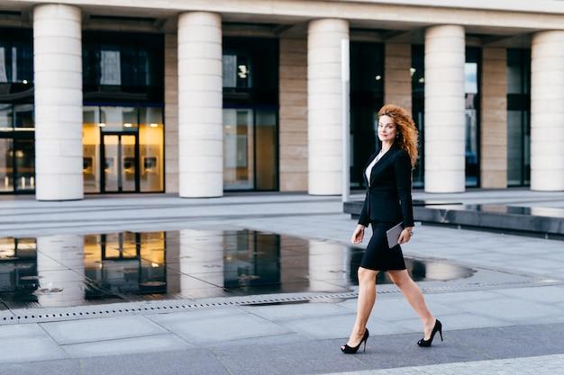 Elegante dünne frau im schwarzen anzug und in den stöckelschuhen, tablette in den händen halten, die arbeit anstreben