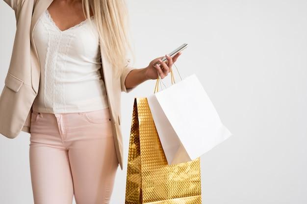 Elegante erwachsene frau, die einkaufstaschen hält