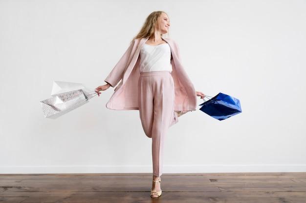 Elegante erwachsene frau, die mit einkaufstaschen aufwirft