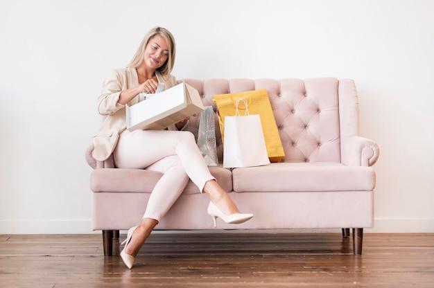 Elegante erwachsene frau, die sich auf dem sofa entspannt