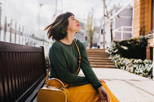 Elegante europäische frau mit dem geraden kurzen haar, das auf bank sitzt. außenporträt des erstaunlichen weißen mädchens trägt grünen pullover im frühlingstag.