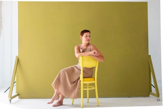 Elegante fällige dame, die auf einem stuhl sitzt