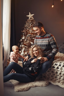 Elegante familie, die zu hause nahe weihnachtsbaum sitzt