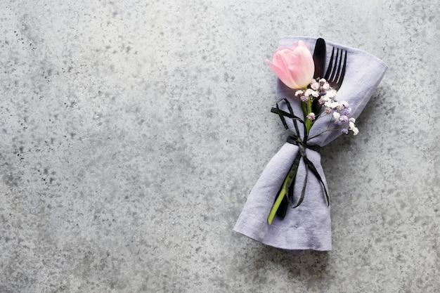 Elegante federtabelleneinstellung mit rosa tulpe auf grau. hochzeit tischdekoration. draufsicht.