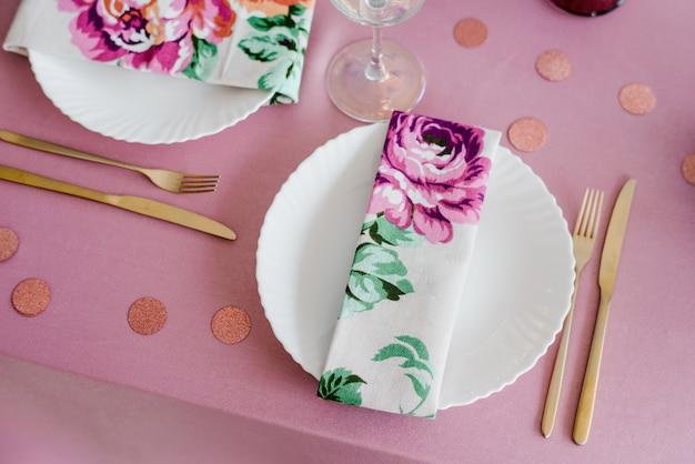 Elegante festliche tischdekoration in rosatönen mit floralen textilservietten, goldener gabel und messer, konfetti. hochzeit, geburtstag, babyparty, mädchenpartydekoration.