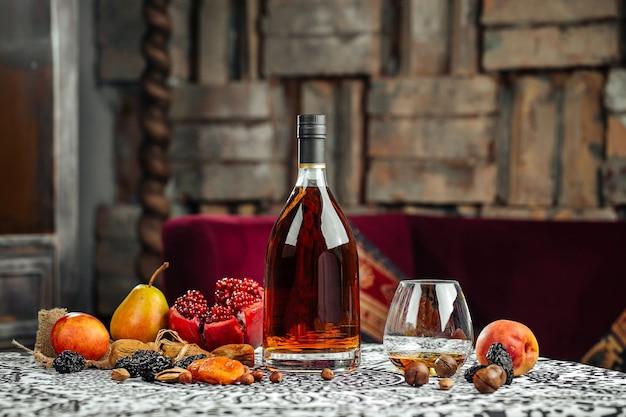 Elegante flasche cognac mit früchten auf dem tisch