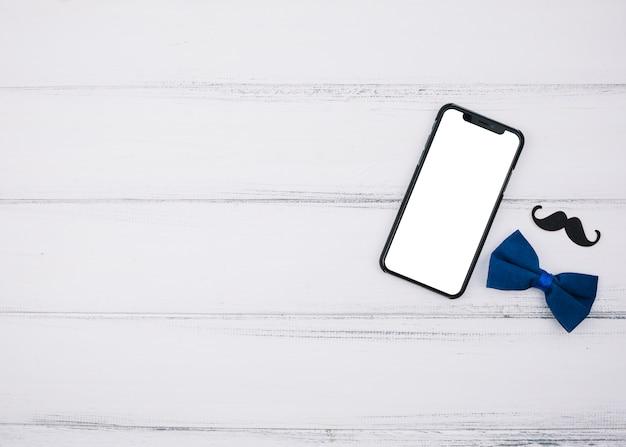 Elegante fliege in der nähe von papierschnurrbart und smartphone