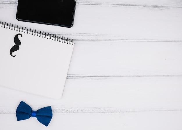Elegante fliege nahe papierschnurrbart auf notizbuch und smartphone