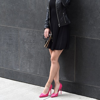 Elegante frau auf high heels mit einem schwarzen kleid und einer lederjacke an der wand