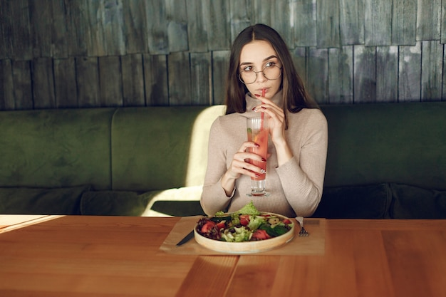 Elegante frau, die am tisch mit cocktail und salat sitzt