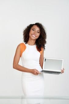 Elegante frau, die an der weißen wand steht und den schirm ihres laptops zeigt