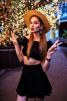 Elegante frau, die an luxushotelterrasse nahe baum mit feiertagslichtern aufwirft