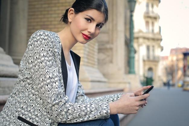 Elegante frau, die auf treppen sitzt und einen smartphone hält