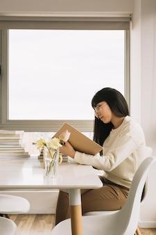 Elegante frau, die bei tisch liest