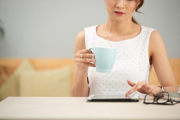 Elegante frau, die bei tisch zuhause sitzt, tablette verwendet und vom becher trinkt
