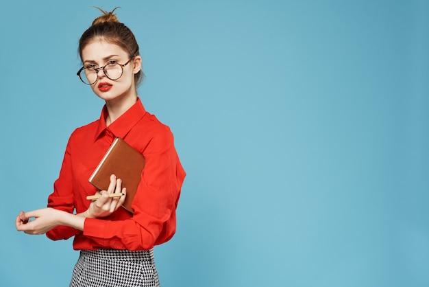 Elegante frau, die brille rotes hemd notizblock sekretär studio trägt