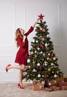Elegante frau, die den weihnachtsbaum verziert