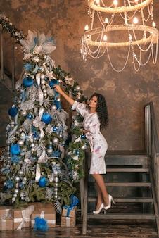Elegante frau, die den weihnachtsbaum verziert.