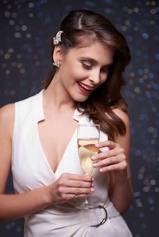 Elegante frau, die ein glas champagner hält