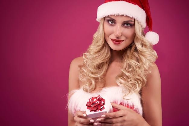 Elegante frau, die ein weihnachtsgeschenk hält