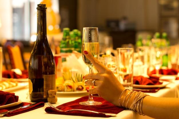 Elegante frau, die eine flöte champagner hält