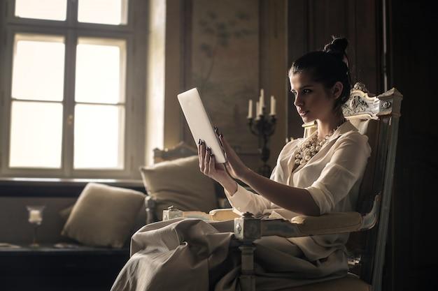 Elegante frau, die eine tablette in einem luxuriösen platz verwendet