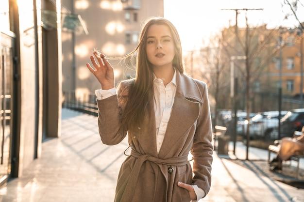 Elegante frau, die einen trendigen braunen mantel trägt, der auf der straße bei sonnenuntergang aufwirft