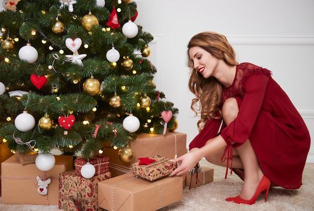 Elegante frau, die geschenke unter weihnachtsbaum setzt