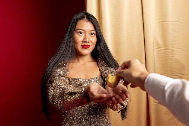 Elegante frau, die glückskeks für chinesisches neues jahr empfängt