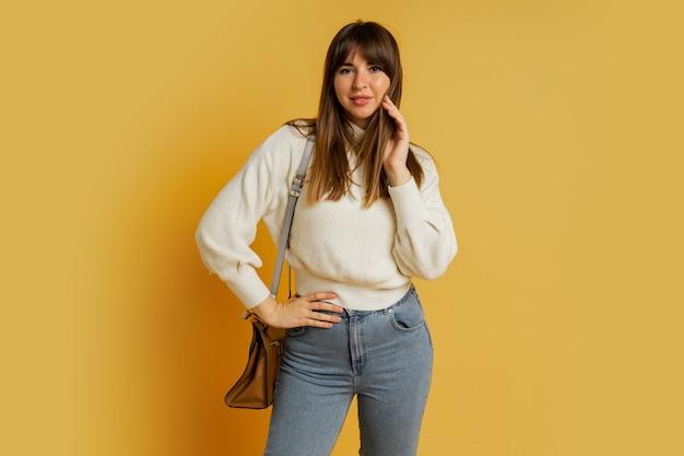 Elegante frau, die im studio auf gelb aufwirft. trägt einen weißen wollpullover und jeans.