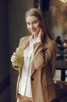 Elegante frau, die in einem café steht und einen cocktail trinkt