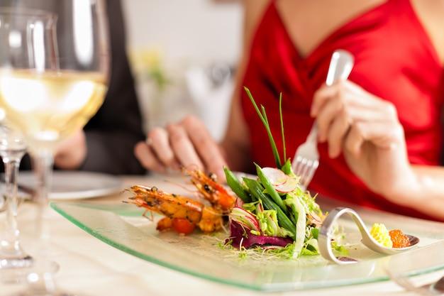 Elegante frau, die in sehr gutem restaurant isst und trinkt
