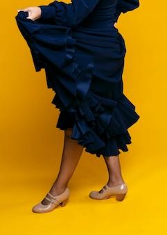 Elegante frau, die kleid mit orange hintergrund anhebt