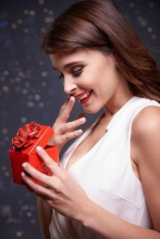 Elegante frau, die kleines weihnachtsgeschenk öffnet