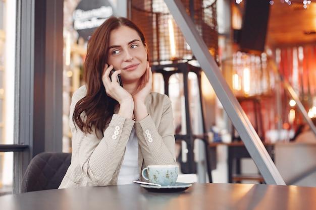 Elegante frau, die mit einem telefon am tisch sitzt